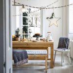 Menej tradičná vianočná výzdoba: kuchyňa s kovovou hviezdou so svetielkami, reťazami z pom pomov a malým stromčekom na sviatočnom stole