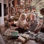 Majiteľka vidieckeho domu vo vianočnej obývačke balí s deťmi darčeky