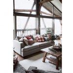 interiér obývačky s presklenou stenou s výhľadom do krajiny, interiér je zariadený vo vianočnom duchu, s menším stromčekom, čečinou a červenými textíliami na sivom gauči