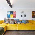 Obývačka so žltou sedačkou so vzorovanými vankúšmi, a kolekciou autorských obrazov