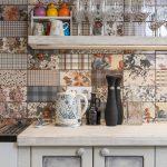 Detail priestoru kuchynskej linky so vzorovaným obkladom a pohármi.