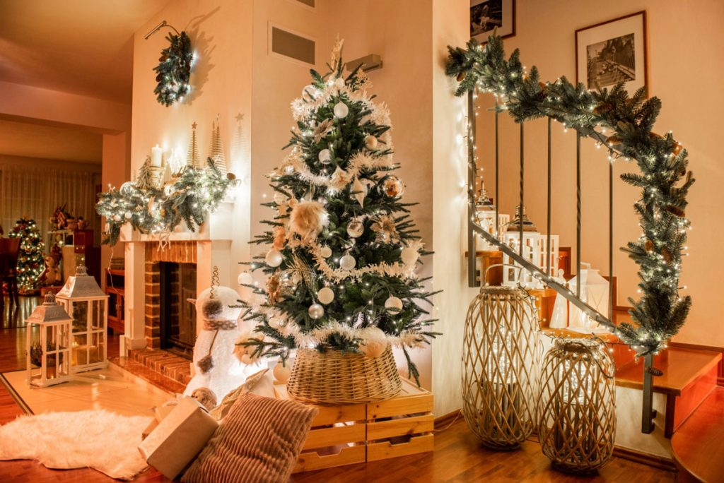 Interiér s vianočnou výzdobou stromček, zábradlie s girlandou, svietniky, krb s girlandou