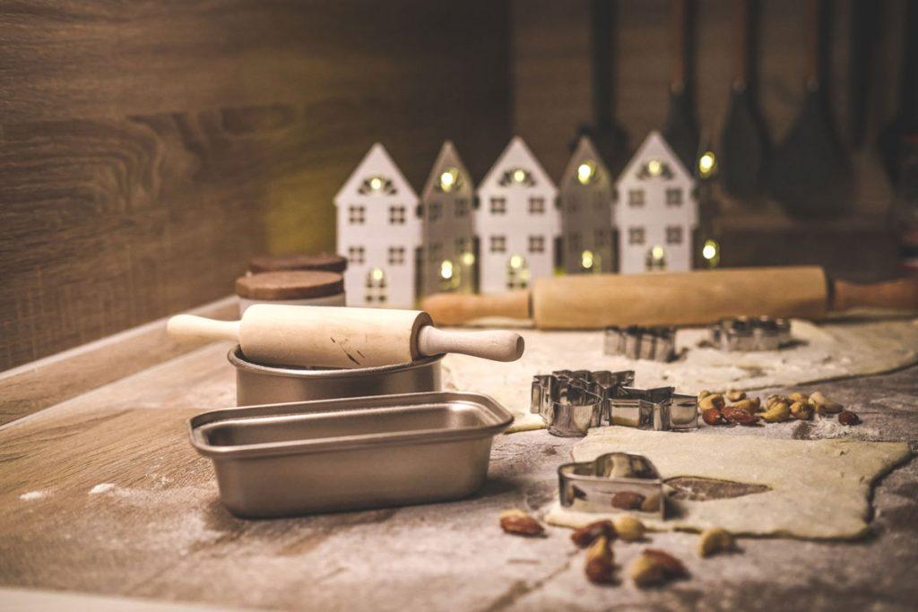 zátišie s vianočným pečením: formičky na vykrajovanie, drevený valček na cesto a svietnik v tvare domčekov
