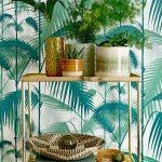 botanický štýl v interiéri: Tapeta so vzorom paliem a zlatý kovový regál s rôznymi druhmi keramických kvetináčov s okrasnými rastlinami