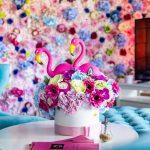 detail kaviarne Pink Garden: váza s kvetinami a pelikánmi, v pozadí s kvetinovou stenou