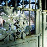 Železná kovaná brána s motívom listov vedúca do storočnej záhrady