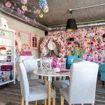 Interiér kaviarne Pink Garden s bielym nábytkom, ružovými doplnkami, kvetinovou stenou a industriálnym betónovým stropom