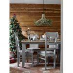 Vianočne vyzdobená jedáleň so stromčekom, zvieracími ozdobami a lustrom s výpletom vyplneným zelenými konárikmi