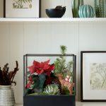 dekorácia s vianočnou ružou umiestnenou v miniskleníku spolu so skalnou ružou, čečinou a soškou jeleňa