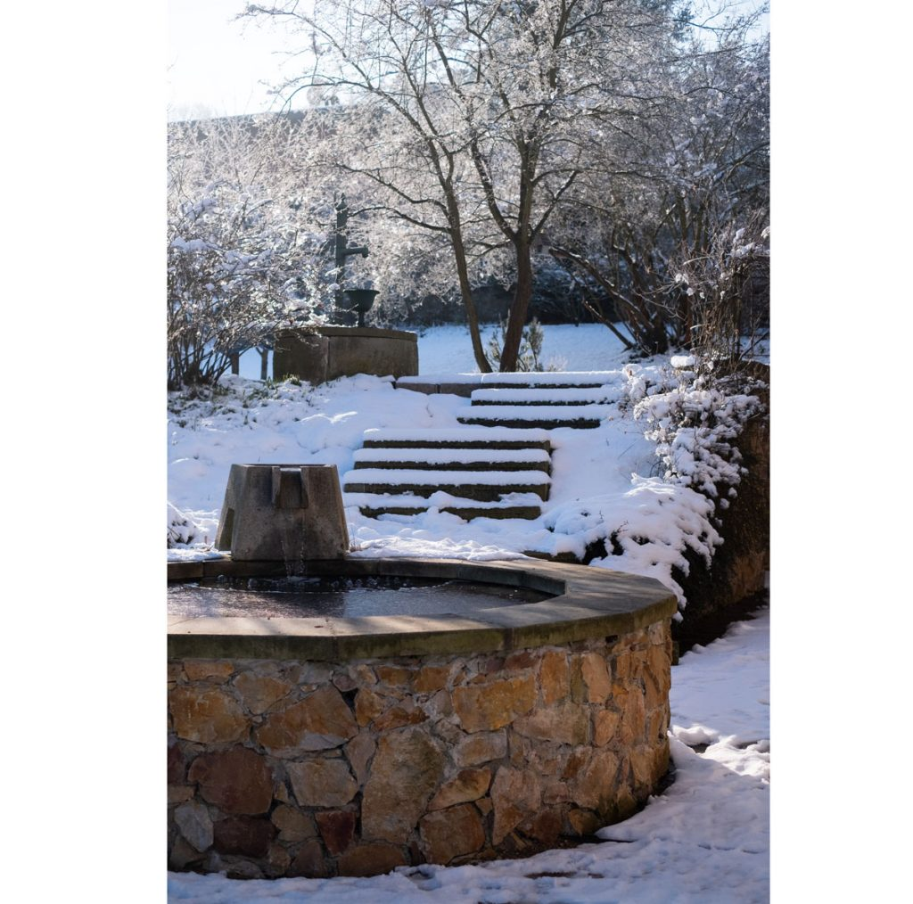 zimná atmosféra v storočnej záhrade: kamenná kruhová fontána od ktorej vedú schody k liatinovej pumpe na vodu