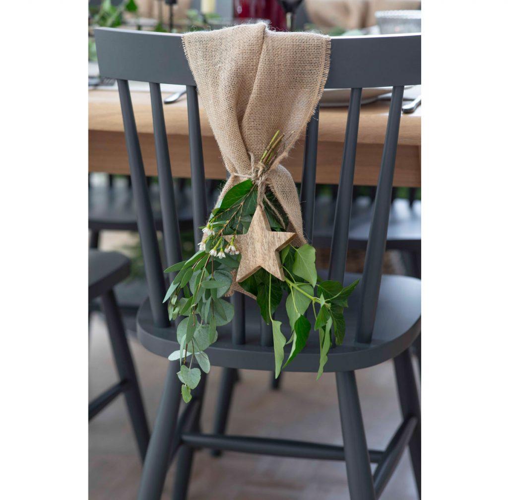 Stolička ozdobená jutovinou s vianočnou drevenou hviezdou a zelenou vetvičkou