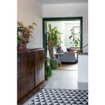 vstupná hala so starožitnou komodou, sivou podlahou a moderným geometrickým kobercom oddelená od obývacej časti zárubňou v zelenej farbe