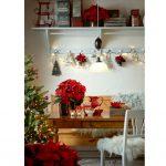 vianočný interiér so stromčekom a rezanými vianočnými ružami umiestnenými vo vázach na stole a na vešiaku