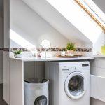 Časť podkrovnej kúpeľne s pultom, pod ktorým je kôš na prádlo a práčka