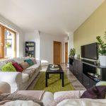 obývačka v podkrovnom byte s východom na terasu, bielou sedačkou, čiernou obývacou stenou a farebnými textíliami