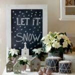 vianočná dekorácia zimnej dedinky s krémovou vianočnou ružou