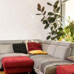 sivá sedačka v obývačke doplnená o červené taburety a farebné vankúše