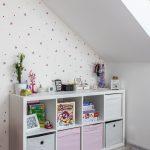 Časť detskej izby s otvorenými policami umiestnenými pod šikmou stenou podkrovného bytu