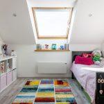 Dievčenská izba v podkroví s čiernou posteľou, bielou otvorenou skrinkou a pestrofarebným kobercom