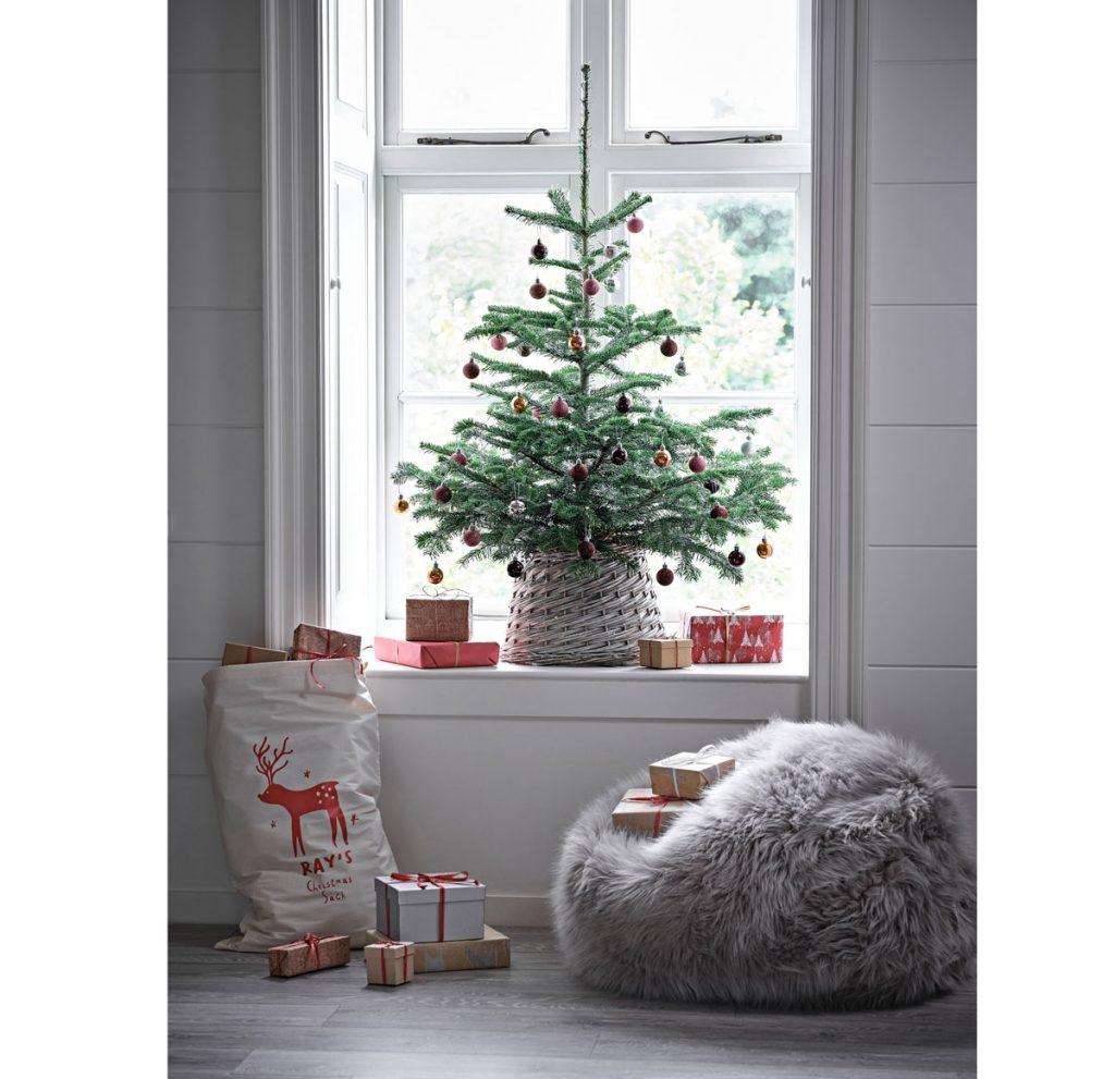 Vianočný stromček v pletenom koši umiestnený v okennom výklenku, pod ním je kožušinový vak na sedenie a vrece na darčeky