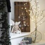 Vianočná výzdoba zložená z vetvičky so svetielkami v sklenenej váze, anjelikov a drevenej dosky s ilustráciou stromčeka