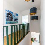 schodisko rodinného domu so zábradlím namaľovaným kriedovou tmavozelenou farbou a s asymetrickou výplňou