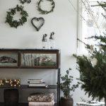 Viacero druhov vianočných vencov zavesených na stene namiesto obrazov