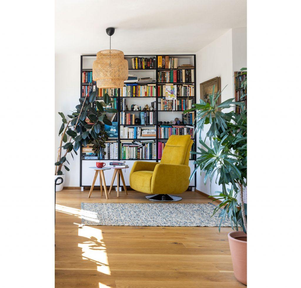 denná miestnosť so žltým otočným kreslom, stolíkmi a knižnicou s čiernym lemovaním