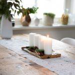 Adventná dekorácia: drevená doska s bielymi sviečkami, vetvičkami, škoricou a šiškami