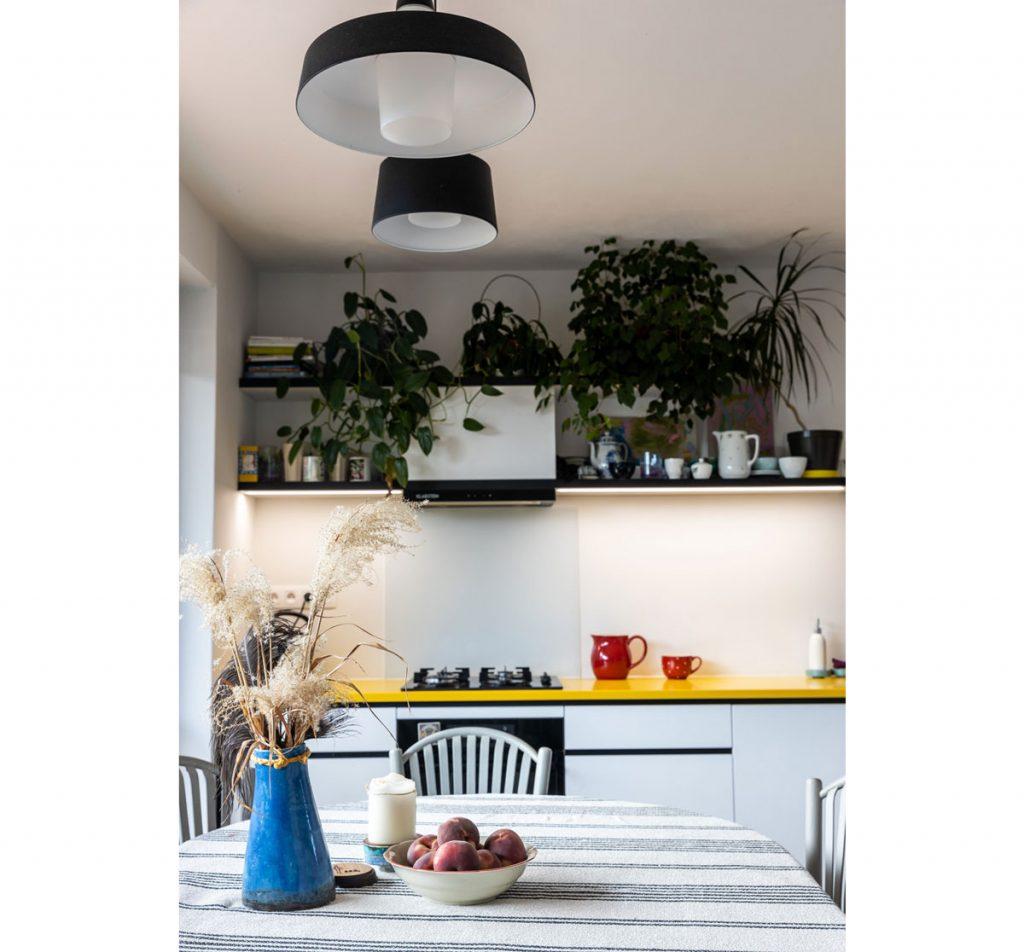 Detail jedálenského stola a kuchynského kútu s výraznou žltou pracovnou doskou a čiernym lemovaním