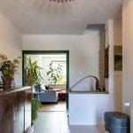 Vstupná hala rodinného domu so starožitnou komodou, kobercom s geometrickým vzorom a vermikompostérom