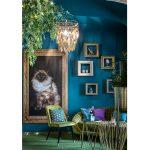 Kaviareň Ragdoll Café: Detail interiéru s veľkým obrazom ragdoll mačky v mohutnom ráme, s glamour sedením v zelenom odtieni, kovovým dekoratívnym stolíkom a obrazovými rámami, ktoré slúžia ako police na dekorácie