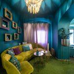 Kaviareň Ragdoll Café: Glamour interiér kaviarne so zelenou pohovkou, zlatými kovovými stolíkmi a zlatým lustrom v tvare lístkov