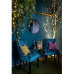 Kaviareň Ragdoll Café: kútik kaviarne s kreslami z modrého zamatu, kovovým stolíkom a stromom olemovaným svetelnými reťazami