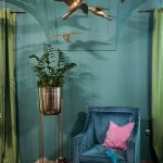 Kaviareň Ragdoll Café: Časť kaviarne so zamatovým modrým kreslom, kovovým stojanom s kvetom a závesnými dekoráciami vtákov