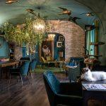 Kaviareň Ragdoll Café: Priestor mačacej kaviarne v glamour štýle, v odtieňoch modrej, zelenej a fialovej, so zlatými doplnkami a dekoráciami s motívom zvierat