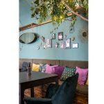 Kaviareň Ragdoll Café: lavicové sedenie s farebnými vankúšmi v mačacej kaviarni pri stene so zvieracími dekoráciami