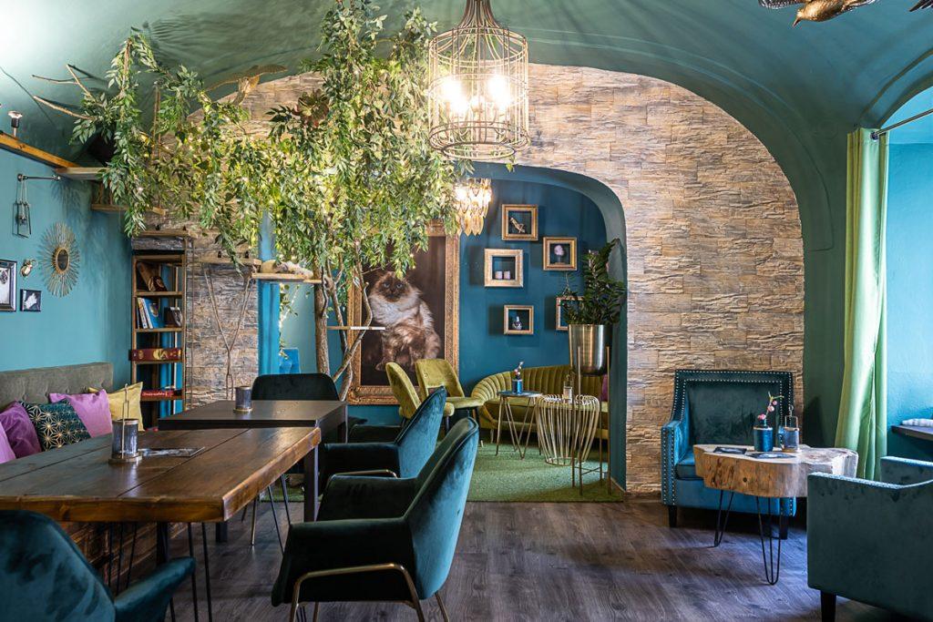 Kaviareň Ragdoll Café: Priestor mačacej kaviarne so zamatovým nábytkom v tmavých odtieňoch modrej a zelenej, s drevenými stolíkmi, zlatými dekoráciami, prechodmi v tvare oblúkov a stromom, ktorý slúži aj ako odpočinková zóna pre mačky
