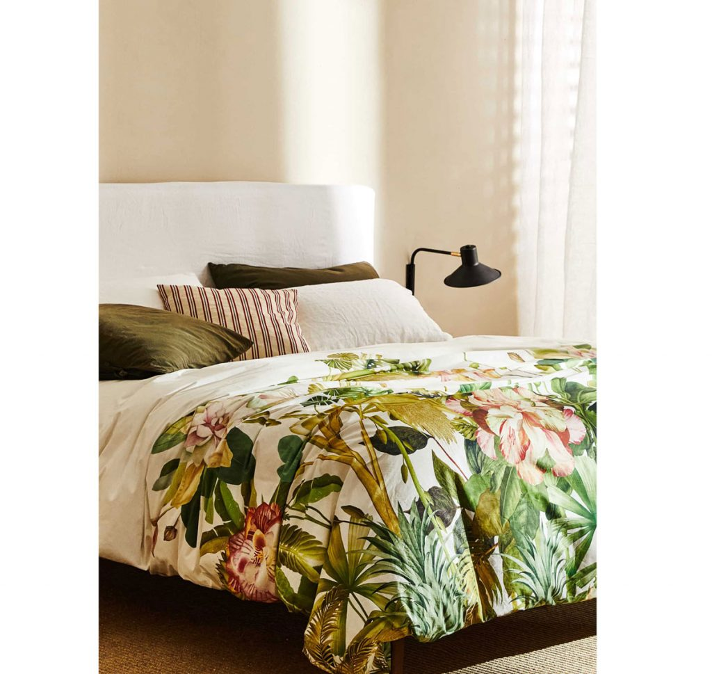 Interiérové trendy roka 2021: posteľ s bavlnenými obliečkami s tropickým motívom