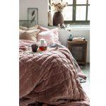 Interiérové trendy roka 2021: Vidiecka spálňa s ružovým posteľným prádlom a starožitným stolíkom