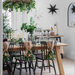 Sviatočne vyzdobená jedáleň s jutovou ozdobou na stoličkách, zeleňou a svetielkami pripevnenými o luster, stromčekom a vianočnými hviezdami