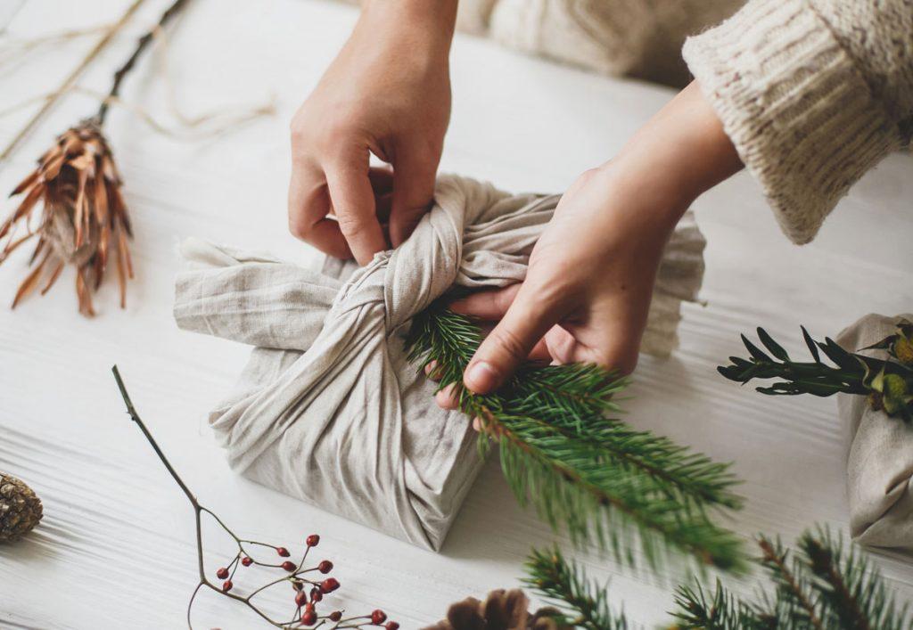 darčeky pod stromček zabalené do látky a dozdobené vetvičkou