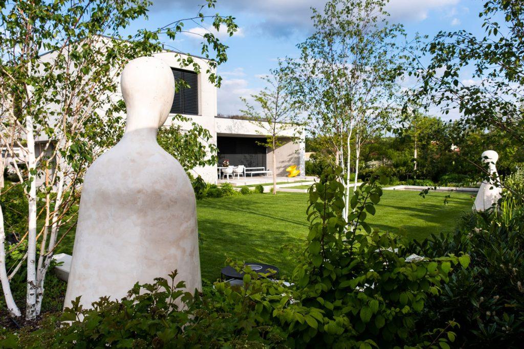 Minimalistická stavba rodinného domu so záhradou s vodným prvkom, terasou na grilovanie a nadrozmernými bielymi sochami autorky Jany Schlosserovej