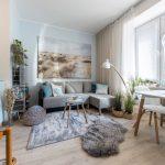Obývačka v stredomorskom a škandinávskom štýle vo svetlých odtieňoch, so sivou sedačkou, bledomodrou stenou, kovovým regálom, izbovými rastlinami a jedálenským stolom