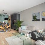 otvorený priestor obývačky a kuchyne vo vzorovom byte v Kolískach, v obývačke je neutrálna modulová sedačka s opačným šitím, v kuchyni dominuje antracitová a tmavozelená farba na minimalistickom zariadení