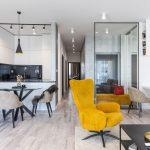 Otvorený priestor dvojizbového bytu v minimalistickom štýle, v neutrálnych odtieňoch s farebným kontrastom na žltom kresle, s priehľadnou stenou deliacou chodbu od obývačky.