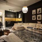 Glamour interiér obývačky spojenej s kuchyňou v kombinácii čiernej a zlatej