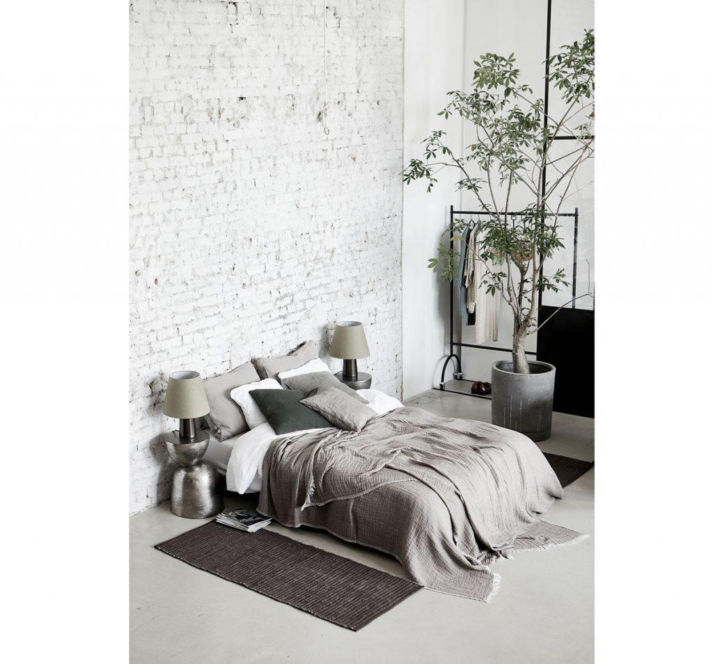 Minimalistická spálňa v neutrálnych farbách, s dizajnovým nábytkom a doplnkami