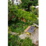 Obnovená mestská záhradka vo vnútrobloku s celoročne atraktívnou výsadbou a terasou so záhradným nábytkom v žlto-bielej kombinácii