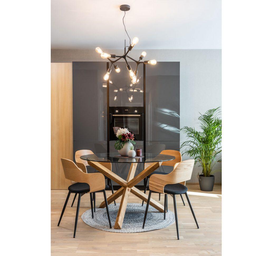 kuchyňa vo vzorovom byte v Kolískach s antracitovou kuchynskou linkou a stenou, skleneným jedálenským stolom s drevenou podnožou, dizajnovými retro stoličkami a dizajnovým viacramenným lustrom